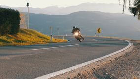 Moto Biker Rides on a Mountain Road from the Turn. Landscape view of the Alps Mountains, Austria. Beautiful Mountain Road. Summer, day stock video