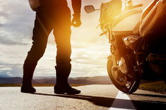 Moto biker road trip closeup concept. Biker stands on straight road with motorbike. Closeup concept Royalty Free Stock Images
