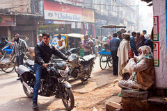 Moto byke driver stoped near the old man. VARANASI, INDIA: Moto byke driver stoped near the old man on the street with active movement of vehicles. Varanasi Royalty Free Stock Photo