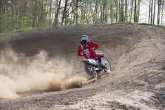 Moto Cross Driver on dusty track - steep turn. Motocross driver on his motorbike driving on a dry and dusty track, approaching a sharp turn / steep turn stock photos