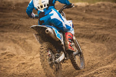 Moto cross - MX girl biker at race in Russia - a sharp turn and the spray of dirt, rear view - close up. Telephoto stock photo