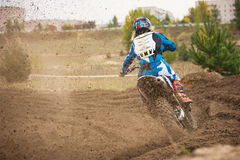 Moto cross - MX girl biker at race in Russia - a sharp turn and the spray of dirt, rear view Stock Image