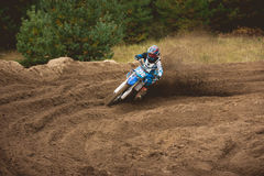Moto cross - MX girl biker at race in Russia - a sharp turn and the spray of dirt Royalty Free Stock Photo