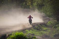 Moto cruza o motorista na trilha empoeirada - conduzindo na poeira fotografia de stock royalty free