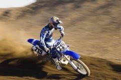 Moto d'équitation de coureur de motocross sur la cendrée images stock