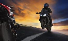 Moto d'équitation de jeune homme sur la route de routes d'asphalte avec des profes image libre de droits