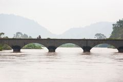 Moto d'équitation d'homme du Laos croisant le pont à travers le Mekong Le Mekong est débordement allant Don Det Island, SI Phan photographie stock