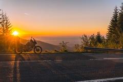 Moto d'aventure, motocyclette touristique de silhouette les crêtes de montagne dans les couleurs foncées du coucher du soleil Cop photos libres de droits