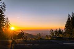 Moto d'aventure, motocyclette touristique de silhouette les crêtes de montagne dans les couleurs foncées du coucher du soleil Cop photographie stock