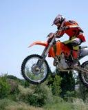 Moto de Moto X que salta a través del aire en un día asoleado caliente con el cielo azul Foto de archivo libre de regalías