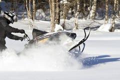 Moto de nieve del montar a caballo con la nieve svirling Fotos de archivo