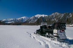 Moto de nieve en las montañas en un día soleado Imágenes de archivo libres de regalías