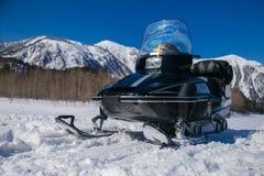 Moto de nieve en un fondo de montañas hermosas Imagen de archivo