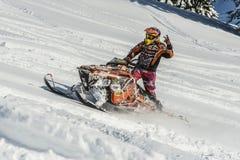 Moto de nieve móvil en bosque del invierno en las montañas Foto de archivo libre de regalías