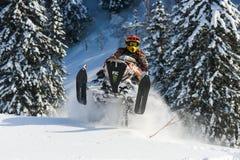 Moto de nieve móvil en bosque del invierno en las montañas Imágenes de archivo libres de regalías