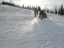 Moto de nieve y esquiadores Imágenes de archivo libres de regalías