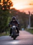 Moto de sportster d'équitation d'homme pendant le coucher du soleil Photographie stock libre de droits
