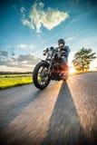 Moto de sportster d'équitation d'homme pendant le coucher du soleil Photos stock