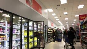 Moto degli alimenti d'acquisto della gente dentro il deposito di Walmart stock footage