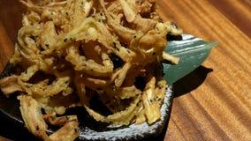 Moto degli aperitivi tagliuzzati fritti nel grasso bollente della bardana sulla tavola video d archivio