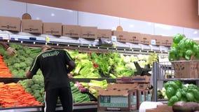 Moto dei broccoli della calza del lavoratore sullo scaffale di esposizione stock footage