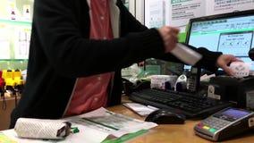 Moto dei clienti che pagano la carta di credito per comprare il propoli dell'ape video d archivio
