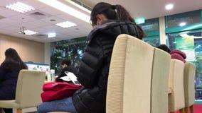 Moto dei clienti che si siedono e che aspettano la Banca dell'interno di servizio stock footage