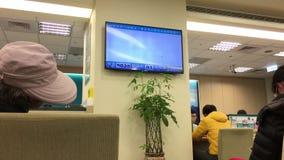 Moto dei clienti che si siedono e che aspettano la Banca dell'interno di servizio archivi video