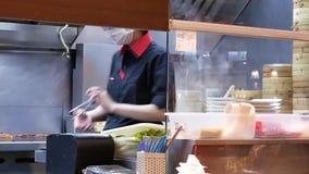 Moto del cuoco unico che cucina alimento per il cliente alla cucina con vapore pesante video d archivio