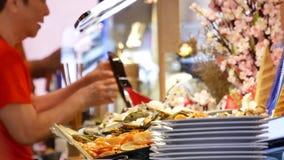 Moto del cuoco unico che prepara alimento per il cliente all'area dei sushi stock footage