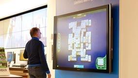 Moto del padre e dei bambini che giocano il gioco del xbox sullo schermo della TV al deposito di Microsoft archivi video