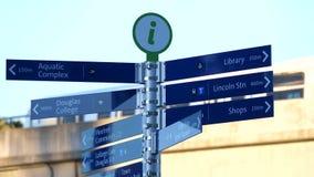 Moto del segnale di informazione di direzione della città con il passaggio dello skytrain della sfuocatura archivi video