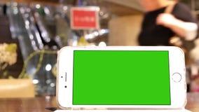 Moto del telefono di schermo verde con la gente della sfuocatura che compera e che riposa archivi video