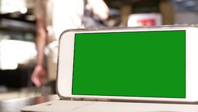 Moto del telefono di schermo verde con la gente della sfuocatura che compera e che riposa stock footage