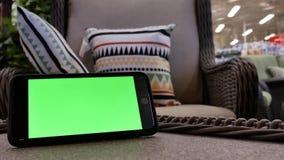 Moto del telefono di schermo verde davanti al sofà dell'esposizione video d archivio