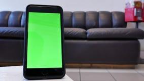 Moto del telefono di schermo verde davanti al sofà dell'esposizione stock footage