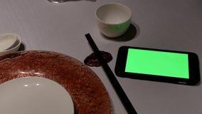 Moto del telefono di schermo verde e del piatto vuoto sulla tavola stock footage