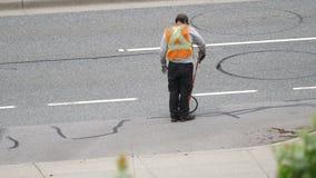 Moto dell'asfalto di riempimento del lavoratore sulla strada dopo la grande stagione di pioggia archivi video