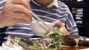 Moto della donna che mangia spigola cotta a vapore con le erbe e la verdura nel servire bianco del piatto stock footage