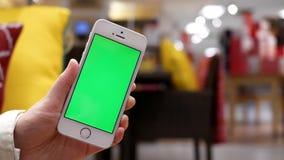 Moto della donna che tiene il telefono cellulare verde dello schermo archivi video
