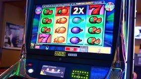 Moto della gente che gioca slot machine dentro il casinò archivi video