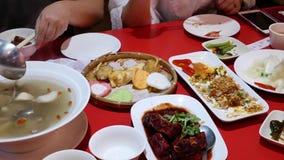 Moto della gente che mangia alimento con la famiglia dentro il ristorante cinese archivi video