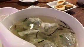 Moto della gente che mangia la minestra e gli aperitivi dello gnocco sulla tavola dentro il ristorante cinese archivi video
