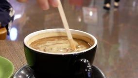Moto della gente che mette crema e che mescola caffè video d archivio