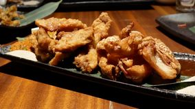 Moto delle ali e della pelle di pollo fritto sulla tavola dentro il ristorante giapponese video d archivio