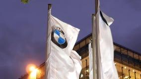 Moto delle bandiere d'ondeggiamento con il logo di BMW alla notte archivi video