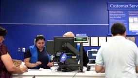 Moto delle merci di ritorno aspettanti della gente al contatore di servizio di assistenza al cliente stock footage