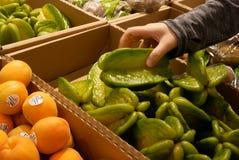 Moto dello starfruit di raccolto della mano del ` s della donna dentro l'ipermercato fotografia stock libera da diritti