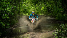 Moto di enduro nel fango con una grande spruzzata Fotografie Stock