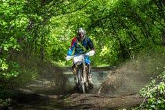 Moto di enduro nel fango con una grande spruzzata Immagine Stock